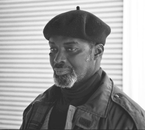 Photo of dark skinned man with gray beard in beret focusing intently to the left