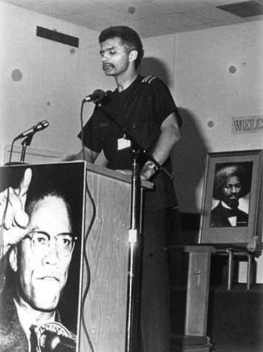 Tall thin New Afrikan man at podium with posters of Malcolm X and Frederick Douglass