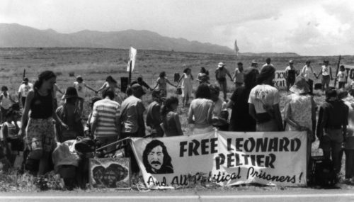 Photo of dozens of people by a roadside holding protest signs including Free Leonard Peltier