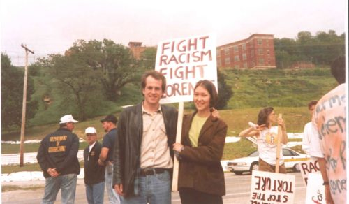 "A woman and man face camera with serious smiles holding placard ""Fight Racism Fight Florence"""