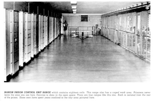 Photo of empty prison corridor with barred cells on all sides