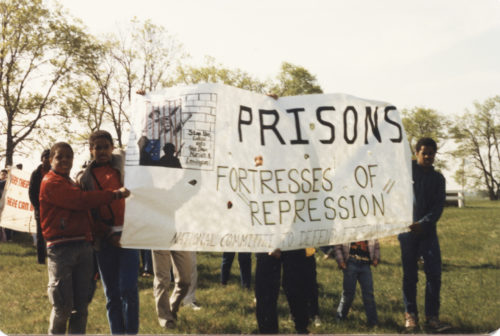 "Half a dozen demonstrators standing on grassy field and holding banner ""Prisons Are Fortresses of Repression"""