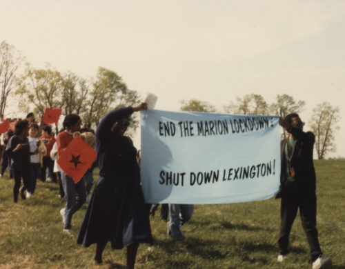 Demonstrators on grassy field holding banner END THE MARION LOCKDOWN! SHUT DOWN LEXINGTON!