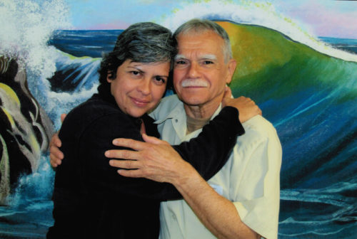 Photo of adult woman with dark hair and serious smile embracing older man with gray hair and mustache