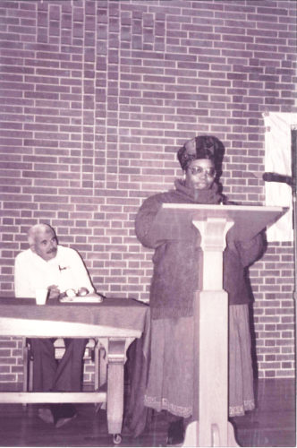 Sepia photo of New Afrikan woman in glasses and headscarf reading from podium with Puerto Rican elder in white shirt behind her looking on