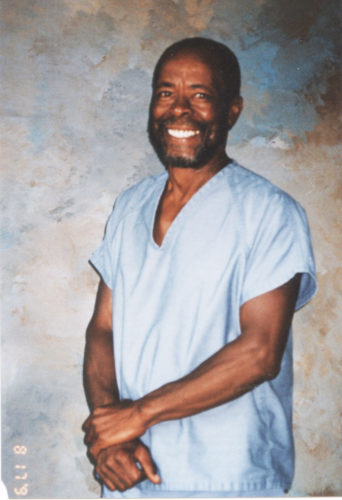 Smiling dark skinned man with beard and broad smile in prison uniform