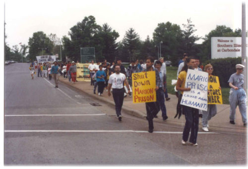 Scores of people marching along the side of a road with protest signs